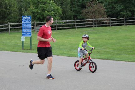 man running alongside child on bike